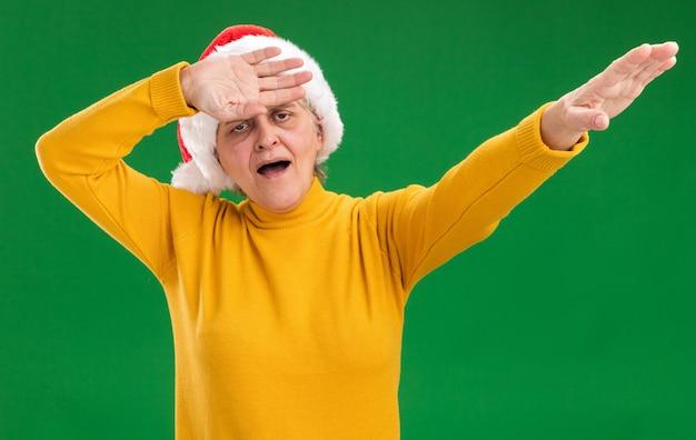 Donna anziana allegra con il cappello di santa che fa il dab isolato sulla parete viola con lo spazio della copia Foto Gratuite