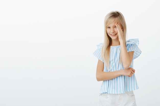 Joyful embarrassed cute girl with long blond hair, covering face from one side with palm and smiling broadly, feeling awkward while father taking picture of her in new outfit