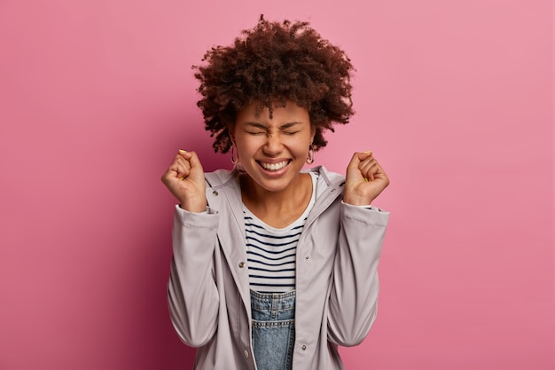 Joyful emotive ethnic curly woman clenches fists, celebates victory, smiles broadly, being in high spirit, closes eyes, wears casual anorak, rejoices achieve goal, poses against pink wall.