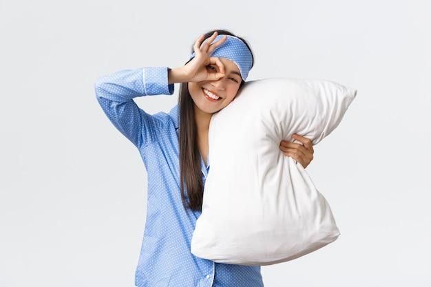 青いパジャマと眠っているマスクでうれしそうな熱狂的な美しいアジアの少女