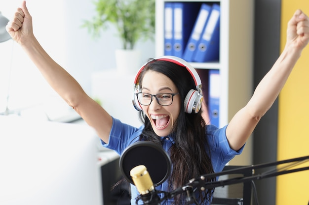 Joyful enthusiastic presenter in headphones with microphone looks at computer monitor sports
