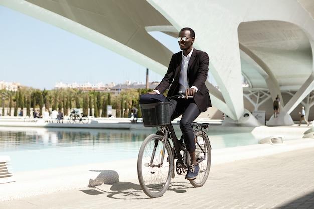 Радостный экологически сознательный африканский офисный работник, одетый в черный строгий костюм и стильные оттенки, выбирающий экологически чистый двухколесный автомобиль на общественном транспорте или автомобиле, чтобы добраться до работы,