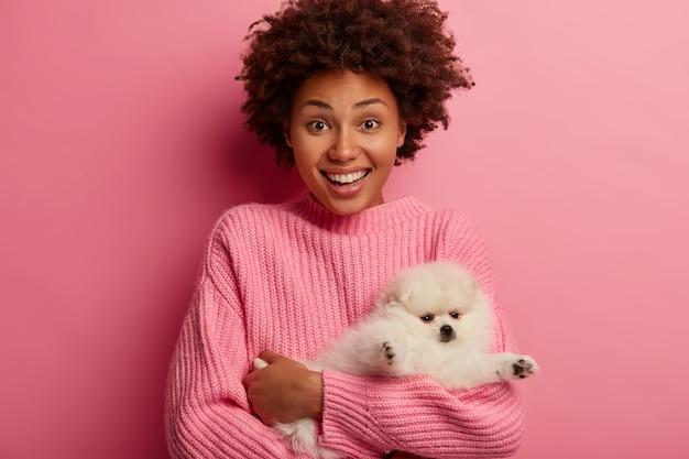 Joyful ethnic girl finds lovely miniature dog on street, being owner of her four legged friend, has good mood, spends free time with favorite pet, wears pink clothing