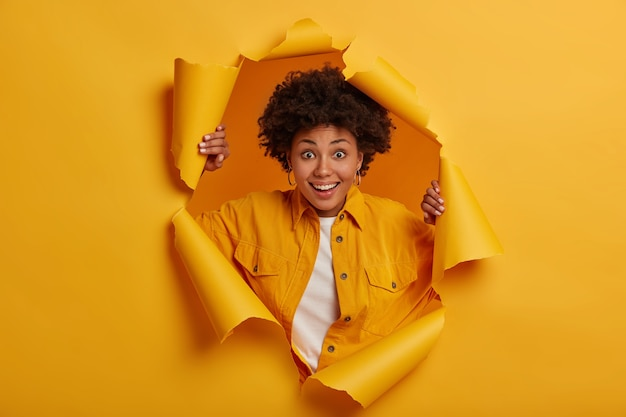 Joyful ethnic woman feels happy, stands through torn hole of yellow background