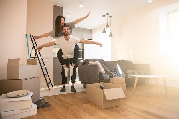 Радостная европейская пара девушки и человека, летящего как птица у себя дома. концепция переезда в новую квартиру. идея молодой семьи. картонные коробки с вещами. интерьер однокомнатной квартиры. солнечный день