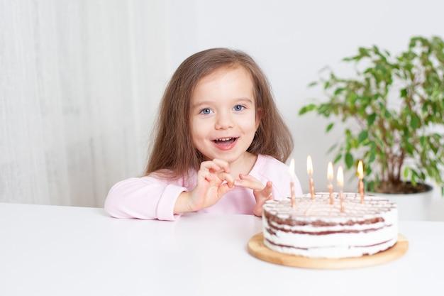 즐거운 유럽 소녀는 그녀의 생일을 축하하고 집에서 케이크 휴일을 먹는다