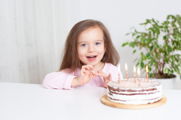 Joyful european girl celebrates her birthday and eats cake holiday at home