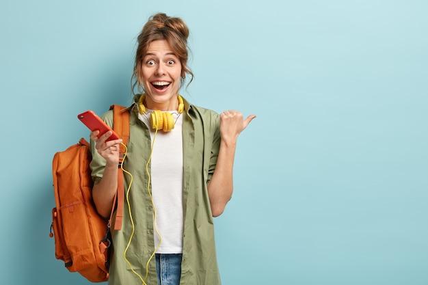 Joyful european girl checks nootification or email box on cellular