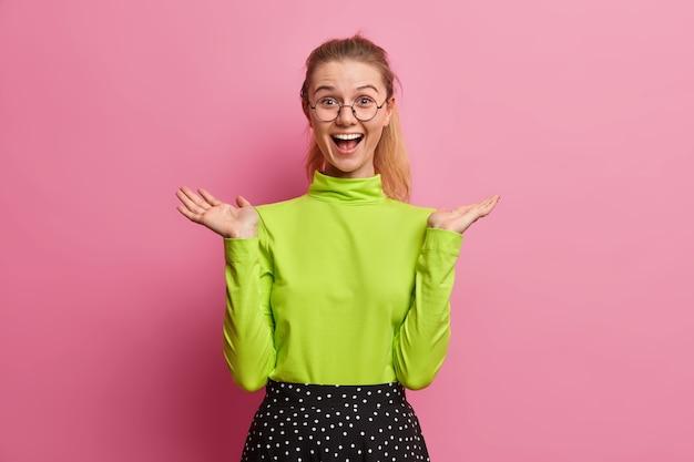 La ragazza europea allegra alza la mano reagisce alle buone notizie