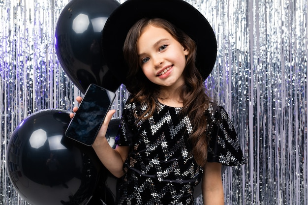 Joyful european girl with a phone with a mockup at a party in the photo zone with black helium balloons and tinsel