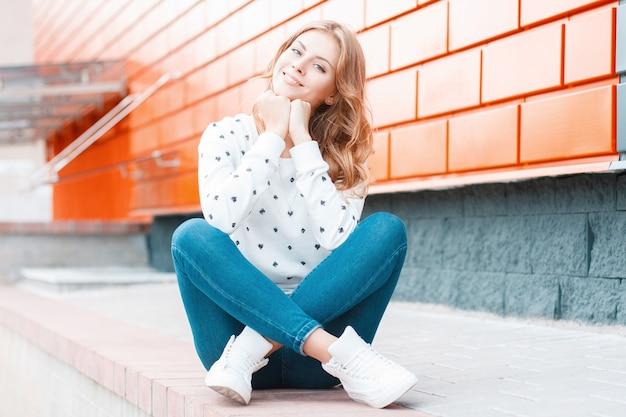 운동화 유행 청바지에 빈티지 스웨터에 즐거운 유럽 젊은 쾌활한 여자가 앉아 거리에 현대 벽돌 건물 근처에 꿈