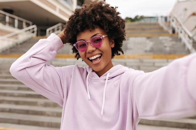 Радостная возбужденная брюнетка в розовых очках и фиолетовой толстовке с капюшоном радуется, улыбается и делает селфи возле лестницы
