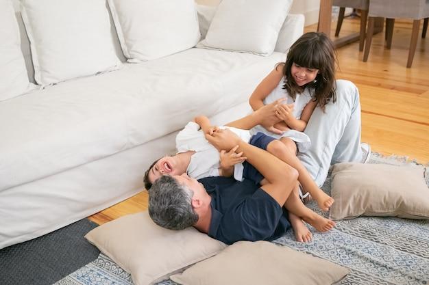 うれしそうな興奮した子供たちが遊んで、お父さんに横になっています。