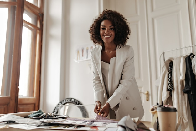 Joyful excited curly dark-skinned woman in oversized white jacket smiles sincerely, looks at front and cuts peace of lace in cozy designer office