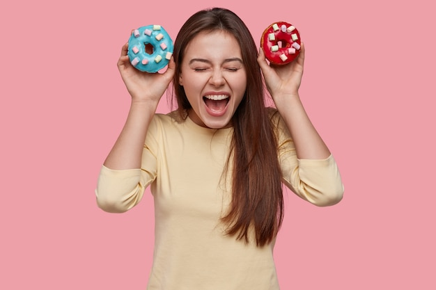 Gioiosa signora eccitata esclama dalla felicità, porta due ciambelle blu e rosse, ha la tentazione di mangiarlo, si tiene a dieta, apre la bocca ampiamente