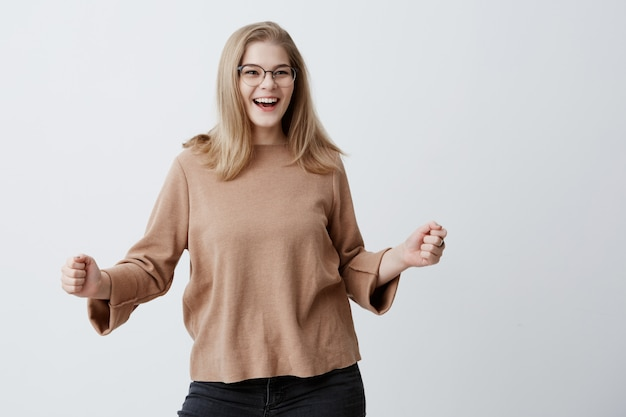 Joyful excited lucky female student with blonde hair and eyeglasses, cheering, celebrating success, screaming yes with clenched fists. success, victory, excitement, and achievement concept.