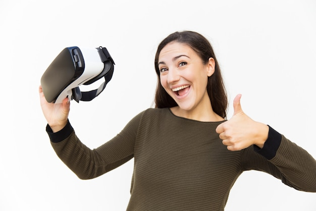 Joyful excited woman holding vr headset and making like