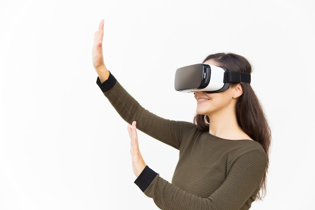 Joyful excited woman in vr headset touching air