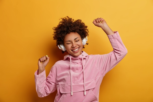 Joyful expressive female listens music in headphones, enjoys pleasant melodies, has good mood, dances carefree, smiles broadly, wears pink sweatshirt, poses against yellow wall. people, leisure