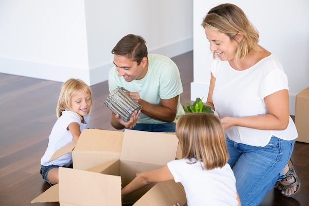 Joyful family couple and adorable girls moving into new flat, having fun while unpacking things in new apartment, sitting on floor and taking objects from open boxes