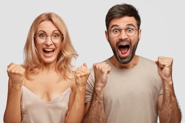 Gioiosa coppia di famiglia riceve buone notizie al mattino, stringe i pugni, esclama con felicità