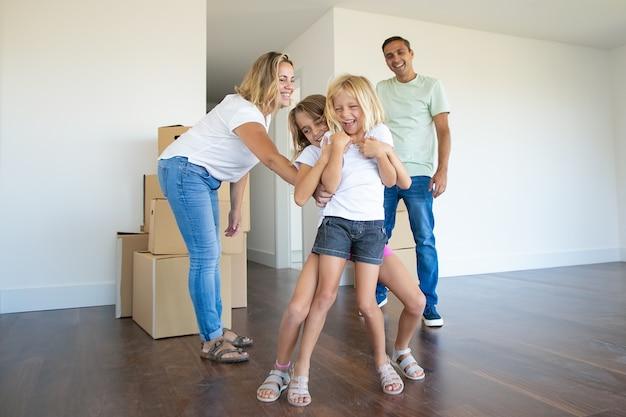 Coppia famiglia allegra e due bambini che si divertono mentre si trasferiscono nel nuovo appartamento