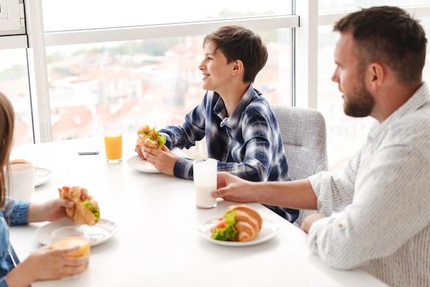 Радостный семейный отец с детьми 8-10, вместе завтракают на светлой кухне дома и едят бутерброды с круассанами