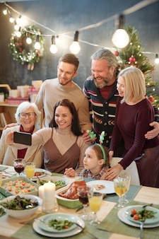 Joyful family of six looking at smartphone  held by young woman while making selfie by served festive table at home