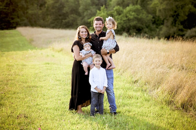 Joyful family with their children and a newborn baby standing on a grassy field