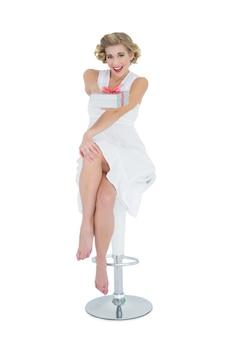 Joyful fashion blonde model offering a gift