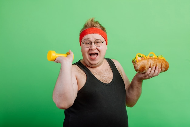 Joyful fat male having fun with burger and dumbbell