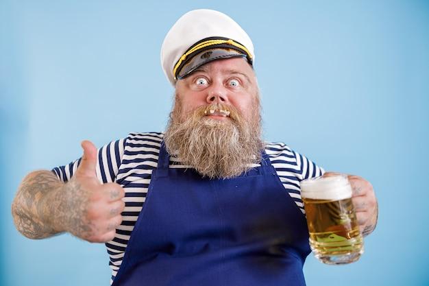 セーラー服のうれしそうな太った人はビールを保持し、水色の背景に親指を表示します