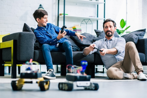 Радостный отец и его сын держат пульты дистанционного управления от современных роботов, наслаждаясь своим хобби