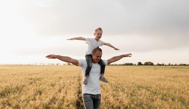즐거운 아버지와 아들은 밀밭을 걷는 재미를 가지고 있습니다.