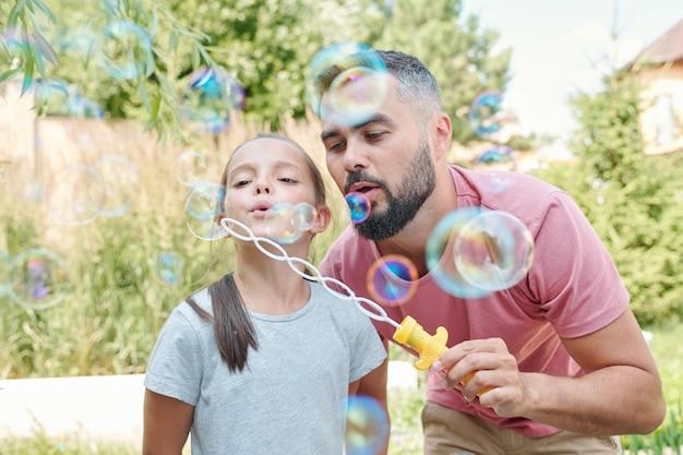 屋外でシャボン玉を吹く彼の素敵な娘と楽しんでうれしそうな父