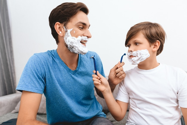 Joyful father and son with foam on faces shaves each other.