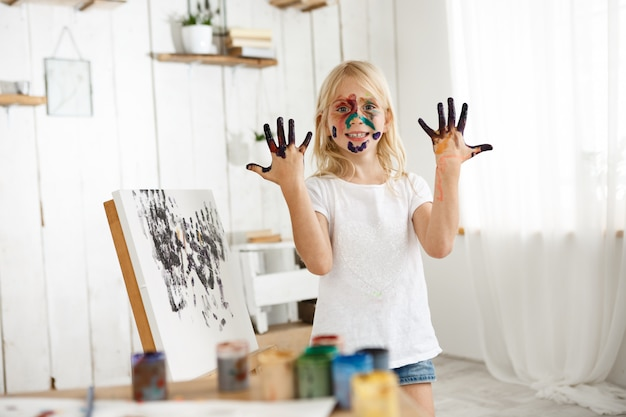 Joyful female caucasian kid demonstrating her hands in black paint, standing behind easle with her picture.