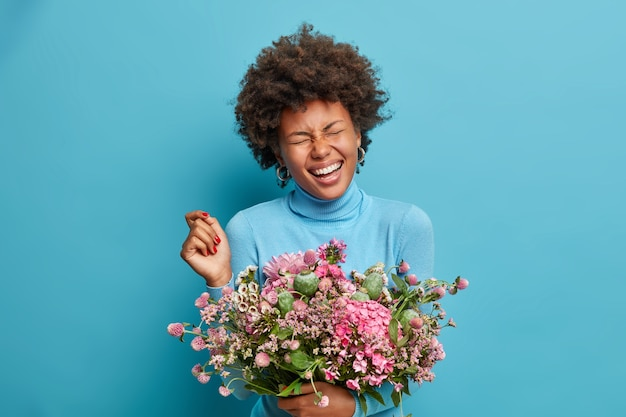 Joyful female florist poses with beautiful bouquet of flowers, laughs happily, has closed eyes, wears blue poloneck, poses indoor.
