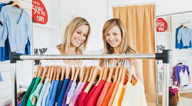 Joyful female friends choosing colorful shirts