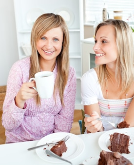 Joyful female friends eating a chocolate cake and drinking in the kitchen
