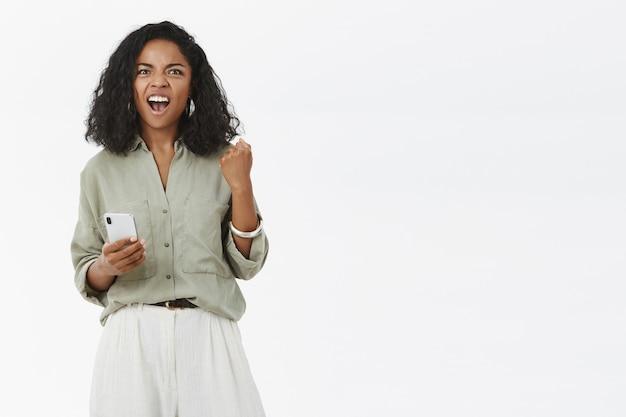 Радостная женщина-габлер чувствует себя взволнованной и счастливой, кричит: да, торжествующе поднимает сжатый кулак