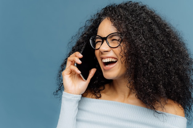 Joyful female has afro hair, laughs happily, talks via cellular, discusses something funny with friend
