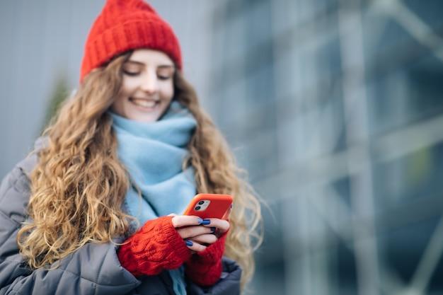 屋外のスマートフォンでタイピングとスクロールの機嫌が良い女性。