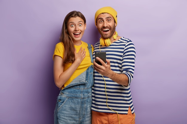 Joyful female and male teenagers hold smartphone gadget, dressed in stylish apparel