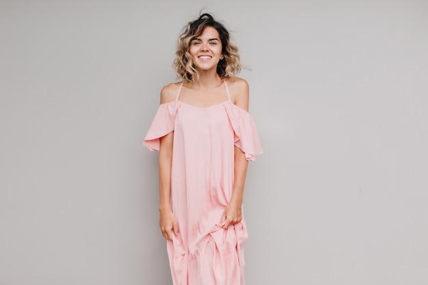 真面目な笑顔でポーズをとる巻き毛のうれしそうな女性モデル。孤立した長いピンクのドレスで日焼けした女の子の屋内写真。