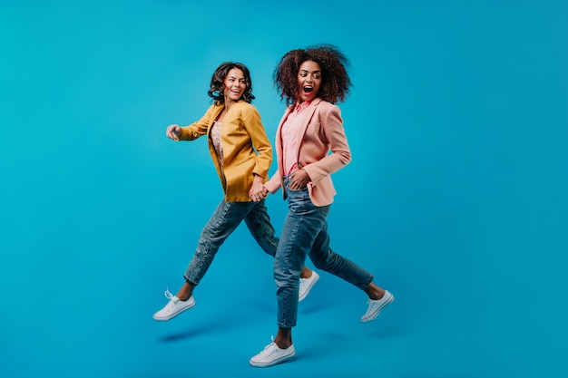 Joyful female models running on blue wall