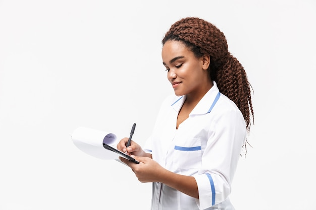 Joyful female nurse writing medical case report isolated against white wall