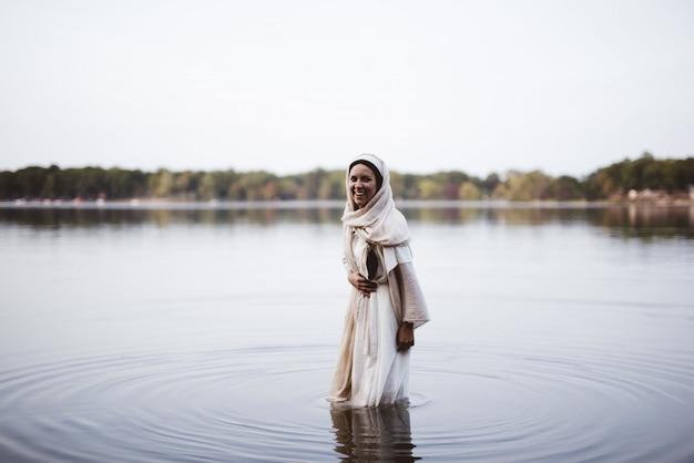 聖書のガウンを着て、水に立っている間笑っているうれしそうな女性