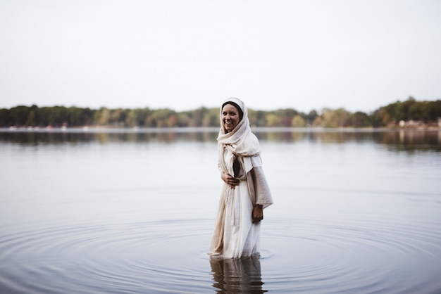 Joyful female wearing a biblical gown and laughing while standing in the water