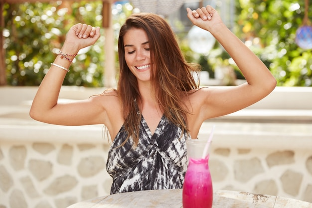 Joyful female with pleasant appearance raises hands, feels pleasure, pretends to dance as hears popular music, being on summer party during recreation in tropical island, drinks fresh fruit cocktail